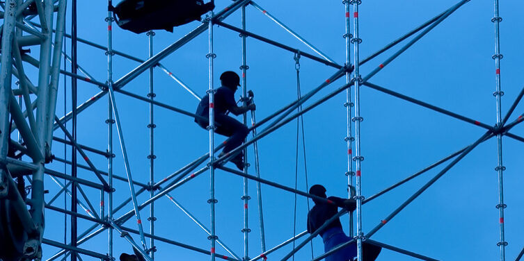 Silhouettes of builders on a background of the sky